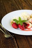 Two strawberries with melissa on plate with fruit dumplings Royalty Free Stock Photo