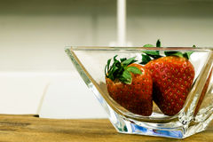 Two strawberries. Red strawberries in a glass rectangular cup Royalty Free Stock Image