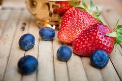 Two strawberries and some grapes blueberries on wooden background. Two strawberries and some grapes a blueberries on wooden background royalty free stock image