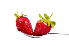 Two strawberries in a spoon Stock Photos
