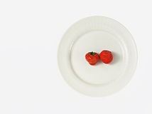 Two strawberries on white plate Stock Images