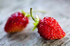 Two strawberries. On wooden background Royalty Free Stock Photos