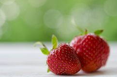 Two strawberries on wooden table Stock Image