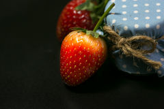 Two strawberry and blue honey button on black background Royalty Free Stock Photo