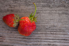 Two strawberry fruits on wooden background. Stock Images