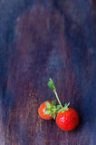 Two strawberry on old wooden table. Strawberry on old wooden table bacground Royalty Free Stock Images
