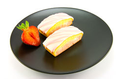 Two Strawberry Slices. Two pink strawberry sliced cakes with icing on the top with a half strawberry on a black plate on a white background Stock Photography