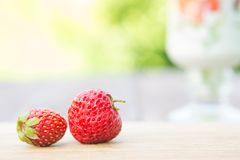 Two strawberryes on cutting board on wooden table over green sunny garden Royalty Free Stock Images
