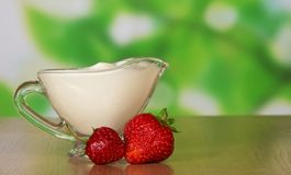 Two strawberrys and cup of cream Royalty Free Stock Image