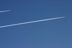 Two stream jet - deux avions -. Two stream jet in high altitude in blue sky stock image