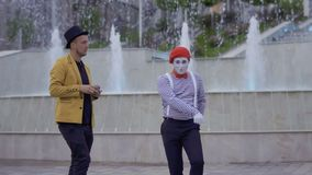 Two street actors fooling around near foutains at urban square. Ilusionist and mime have fun standing near the illuminated fountains at the urban street. Two stock video
