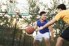 Two street basketball players on the basketball court Stock Photos