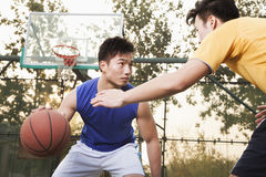 Two street basketball players on the basketball court Stock Images