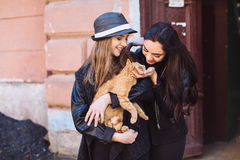 Two street girls with a cat Stock Photo