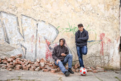 Two street hooligans standing against a graffiti pain Stock Photo