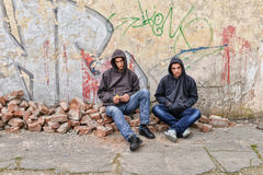 Two street hooligans standing against a graffiti painted wall are preparing to smoke a cigarette Royalty Free Stock Images