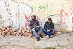 Two street hooligans standing against a graffiti painted wall Royalty Free Stock Images