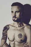 Young naked man with tattoos on the body. Portrait of a young naked man with tattoos on the body royalty free stock photo