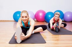 Two stretching girls Stock Photos