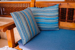 Two striped cushions lie on a wooden sofa Royalty Free Stock Photos