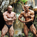 Two strong bodybuilders posing outdoors Royalty Free Stock Photos