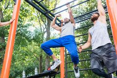 Two strong and competitive men exercising on monkey bars. Low-angle view of two strong and competitive men exercising on monkey bars for the upper-body in a Royalty Free Stock Photography
