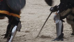 Two strong knights wearing steel armor fighting actively, medieval tournament. Stock footage stock video footage