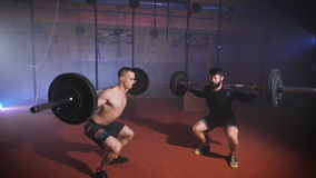 Two strong man doing weightlifting training together at the gym. Two strong man doing syncrhonized weightlifting training together at the gym. Barbell jump stock video