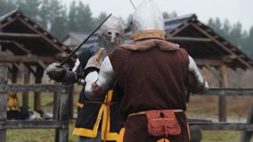 Two strong men wearing armour reenacting duel between brave medieval knights. Stock footage stock footage