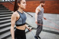 Two strong people are jumping using a rope for that. Guy is jumping more intensive that girl does. He is looking down. While she is looking straight forward Stock Images