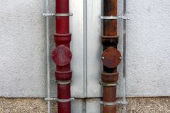 Two strong rusted metal gutter rainfall pipes connected to lightning rod on both sides mounted on side of local apartment building. On warm sunny spring day stock image