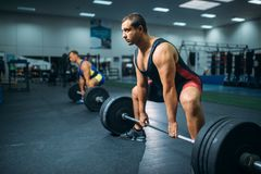 Two weightlifters doing exercise with barbells stock images