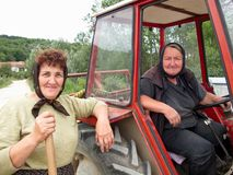 Two really strong women and a tractor. Portrait of two really very strong women with tractor going to fields royalty free stock images