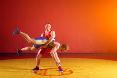 Two young men  wrestlers. Two strong wrestlers in blue and red wrestling tights are wrestlng and making a  making a hip throw  on a yellow wrestling carpet in Stock Photography