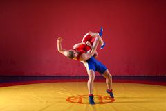 Two young men  wrestlers. Two strong wrestlers in blue and red wrestling tights are wrestlng and making a  making a hip throw  on a yellow wrestling carpet in Royalty Free Stock Images