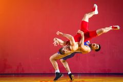 Two strong wrestlers. In blue and red wrestling tights are wrestlng and making a making a hip throw on a yellow wrestling carpet in the gym. Young men doing Royalty Free Stock Photos
