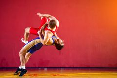 Two strong wrestlers. In blue and red wrestling tights are wrestlng and making a  making a hip throw  on a yellow wrestling carpet in the gym. Young men doing Stock Photo
