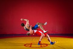 Two strong wrestlers. Two young men wrestlers in blue and red wrestling tights are wrestlng and making a hip throw on a yellow wrestling carpet in the gym, sied stock images