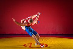 Two strong wrestlers. Two young men wrestlers in blue and red wrestling tights are wrestlng and making a hip throw on a yellow wrestling carpet in the gym, sied Royalty Free Stock Photography