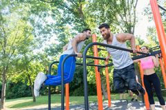 Two strong young men doing dips exercise for the upper body outdoors. Two strong and motivated young men doing dips exercise for the upper body, during stock images