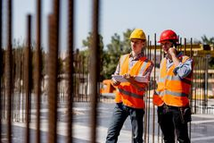 Two structural engineers dressed in shirts, orange work vests and helmets explore construction documentation and talk by royalty free stock photography