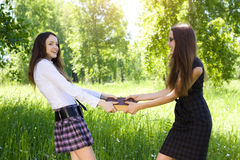 Two student girl taken one same book outdoor Royalty Free Stock Photo