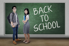 Two students back to school and standing in class. Portrait of two high school students back to school and standing in the classroom while smiling at the camera Royalty Free Stock Image