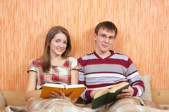 Two students with books at home Stock Photos