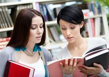 Two students with books at the library Stock Images