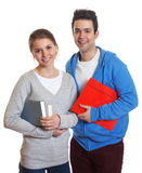 Two students with books and paperwork looking at camera. Two students laughing at camera on an isolated white background Stock Photography