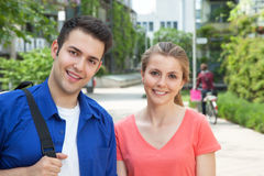 Two students on campus laughing at camera. Attractive two students young on campus of the University laughing at camera Royalty Free Stock Photography