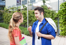 Two students on campus speaking about the studies. With university building in the background Royalty Free Stock Image