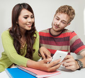 Two students checking a handphone. A portrait of two students checking a handphone while studying Royalty Free Stock Photos