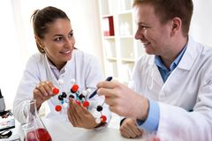 Two students of chemistry looking at molecular model and making Stock Image